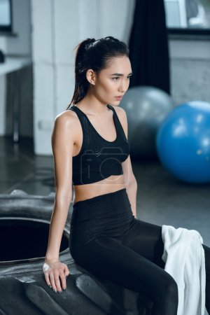young sporty woman sitting on workout wheel after training at gym