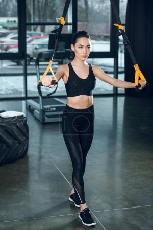 young sporty woman working out with resistance bands at gym