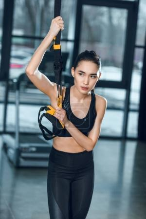 Photo for Young sporty woman working out relaxing at gym while leaning on suspension straps - Royalty Free Image