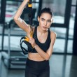 Young sporty woman working out relaxing at gym whi...