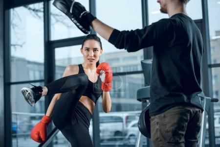 Photo for Young female fighter performing low kick with trainer at gym - Royalty Free Image