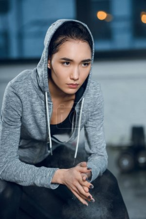 young fit woman clapping hands with talc before workout at gym