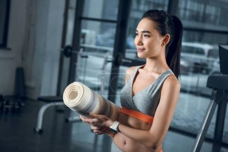 young sporty woman with rolled yoga mat at gym