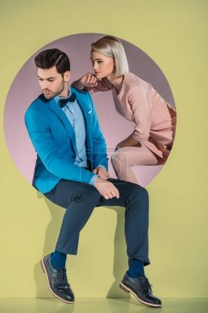 beautiful couple in stylish clothes looking down on yellow