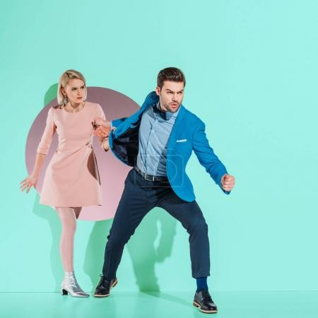 angry boyfriend going with fashionable girlfriend through aperture on turquoise