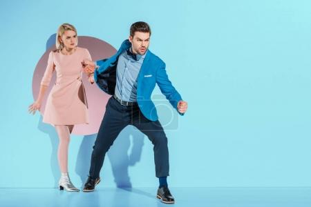 angry boyfriend going with fashionable girlfriend through aperture on blue