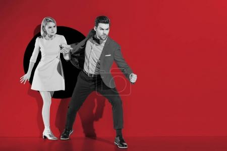 angry boyfriend going with fashionable girlfriend through aperture on red