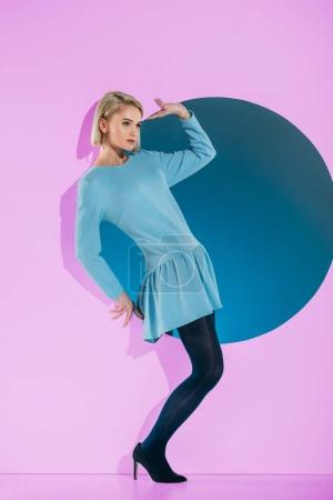 beautiful girl in fashionable clothes posing on pink