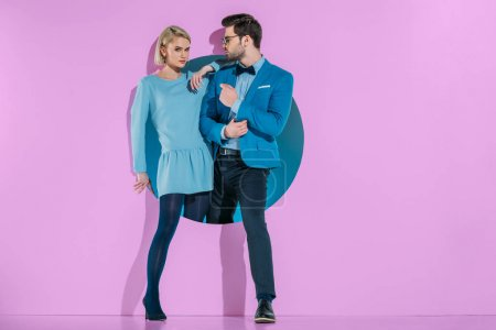 attractive stylish couple stepping through aperture on purple
