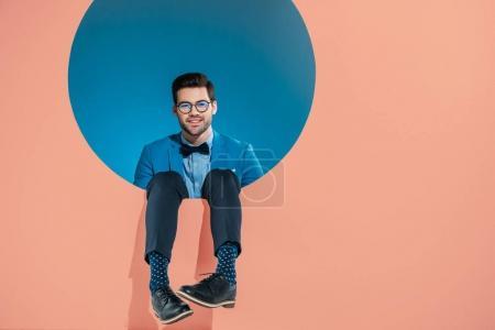 souriant bel homme dans des vêtements à la mode, assis dans un cadre rond sur beige