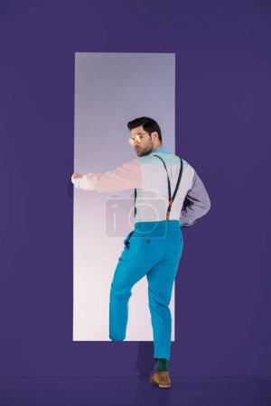 rear view of handsome man in fashionable clothes going through frame on purple