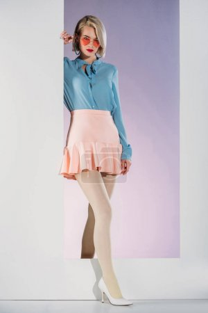 beautiful girl in fashionable clothes standing in frame and looking at camera on white