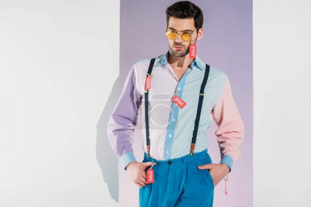 handsome man in stylish clothes with sale tags standing isolated on white