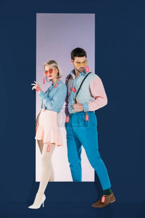 attractive couple in fashionable clothes with sale tags isolated on blue