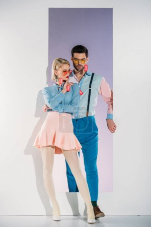 attractive couple in fashionable clothes with sale tags on white