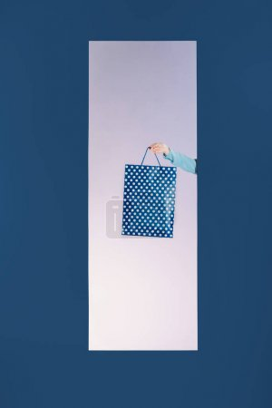 cropped image of girl holding shopping bag in frame isolated on blue