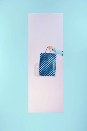 cropped image of girl holding shopping bag in frame isolated on turquoise
