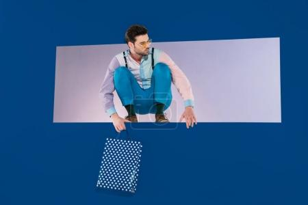 handsome man in stylish clothes squatting with shopping bag isolated on blue