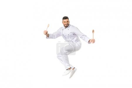 young male chef with utensils jumping and smiling at camera isolated on white
