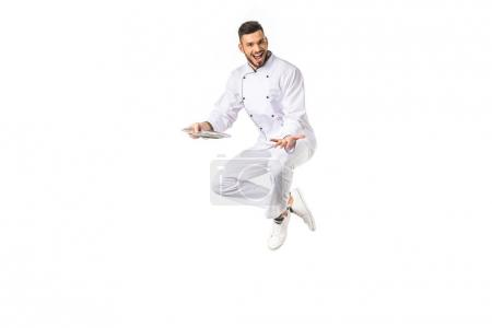 Photo for Happy young male chef with plate jumping and smiling at camera isolated on white - Royalty Free Image