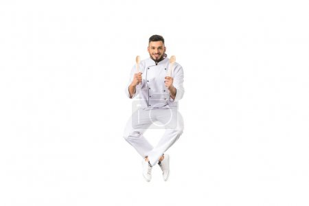 Photo for Happy young chef holding utensils and smiling at camera isolated on white - Royalty Free Image