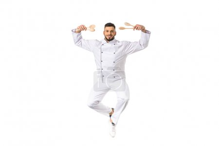 young male chef holding utensils and smiling at camera isolated on white