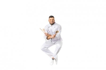 Photo for Young man chef with utensils jumping and smiling at camera isolated on white - Royalty Free Image
