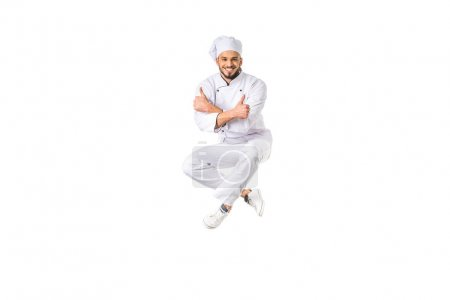 happy young male chef showing thumbs up and smiling at camera isolated on white