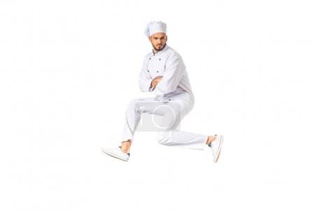 handsome young male chef jumping and looking at camera isolated on white