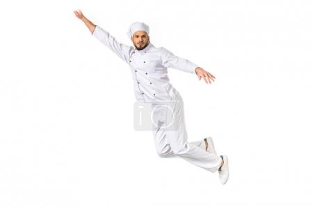 young male chef with raised hand flying and looking at camera isolated on white