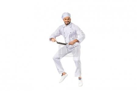 Photo for Happy young chef holding frying pan while jumping and smiling at camera isolated on white - Royalty Free Image