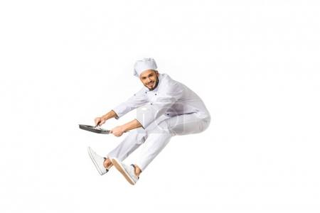 happy young chef with frying pan jumping and looking at camera isolated on white