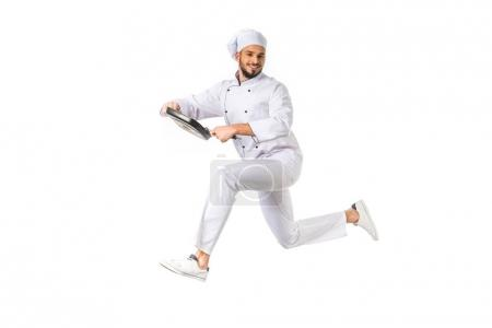 smiling chef with frying pan jumping and looking at camera isolated on white