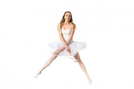 beautiful young ballerina dancing and smiling at camera isolated on white