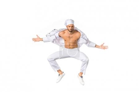 handsome young bare chested chef jumping and looking at camera isolated on white