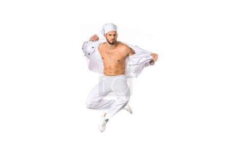 handsome young bare chested chef jumping isolated on white