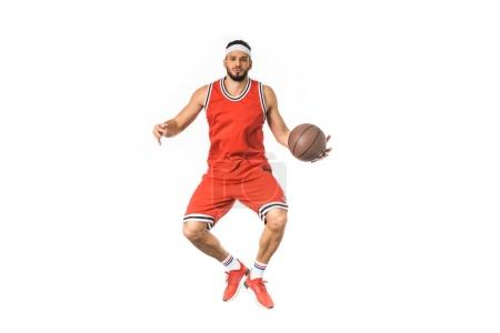 handsome young basketball player jumping with ball and looking at camera isolated on white