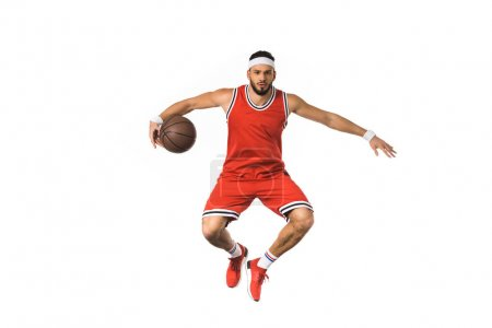 young basketball player jumping with ball and looking at camera isolated on white