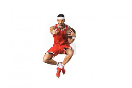 young basketball player holding ball and pointing at camera with finger isolated on white