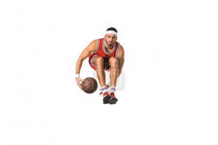 young basketball player with ball jumping and looking at camera isolated on white