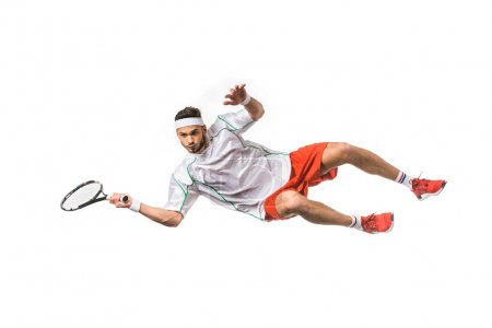 Photo pour Beau sportif jeune jouant au tennis en saut isolé sur blanc - image libre de droit