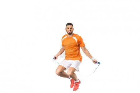 young man jumping with skipping rope and smiling at camera isolated on white