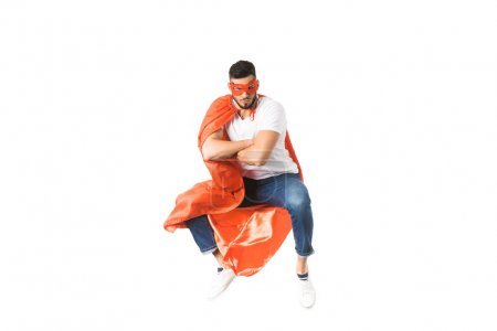 Photo for Young man in red cloak and mask jumping with crossed arms and looking at camera isolated on white - Royalty Free Image