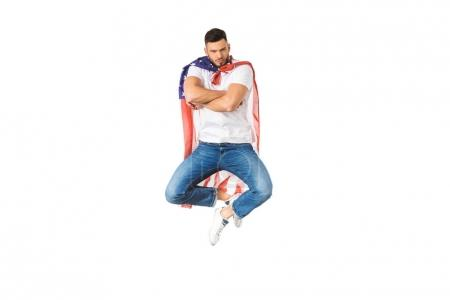 handsome young man with american flag jumping with crossed arms and looking at camera isolated on white