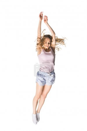 full length view of smiling young woman with raised hands jumping and looking down isolated on white