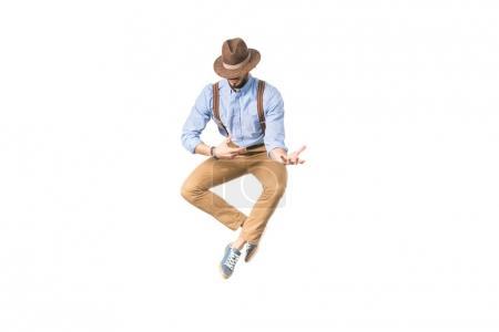 Photo pour Élégant jeune homme au chapeau sautant et gesticulant avec mains isolés sur blanc - image libre de droit