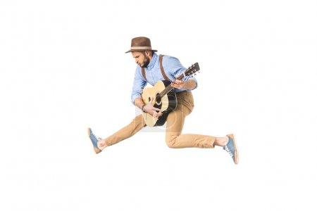 handsome young musician in hat playing guitar while jumping isolated on white