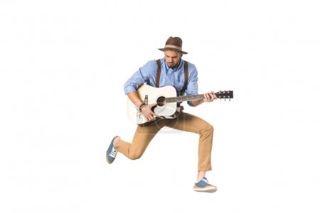 handsome young musician in hat playing guitar and jumping isolated on white