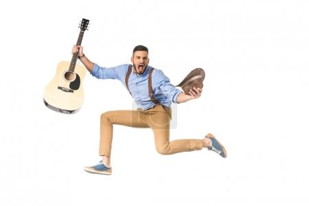 excited young musician with guitar and hat screaming at camera isolated on white