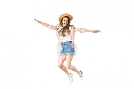Foto de Happy girl in hat jumping with open arms and smiling at camera isolated on white - Imagen libre de derechos